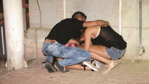 אנשים מוצאים מחסה ומתגוננים בעת נפילת טיל בבאר־שבע