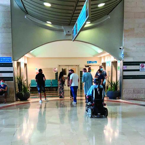 תשעה אנשים ממתינים בתור למעליות בבית החולים